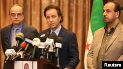 File - Khaled Khoja (center), the head of the Syrian National Coalition, speaks during a press conference as the former Secretary General Nasr Hariri, right, and the former president Hadi Bahra, left, stand next to him, in Istanbul, Turkey, January 2015.
