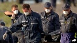Nhân viên cấp cứu mang thi thể nạn nhân ra từ địa điểm tai nạn gần làng Hrabove, đông Ukraine.