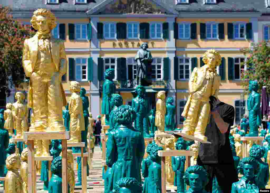 A worker sets up one of hundreds of Ludwig van Beethoven plastic sculptures designed by German conceptual artist Ottmar Hoerl to mark the 250th birth anniversary of the German composer, in Bonn.