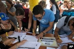 FILE - People sign a petition, organized by the opposition, to initiate a recall referendum against Venezuela's President Nicolas Maduro in Caracas, April 27, 2017.