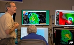 VD direktora Nacionalnog centra za uragane, Ed Rapaport, levo i viši specijalista za uragane Ričard Paš posmatraju na monitorima uragan Irmu u Nacionalnom centru za uragane u Majamiju, 10. septembra 2017.