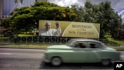 "A man drives a vintage American car next to a display — which reads ""Welcome to Cuba Pope Francis"" in Spanish — at Revolution Square in Havana, Cuba, Sept. 15, 2015."
