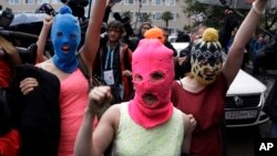 Pussy Riot üyelerinden Nadezhda Tolokonnikova (mavi kar maskeli) ve Maria Alekhina (pembe kar maskeli) gözaltından sonra serbest bırakıldı.