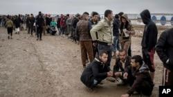 FILE - Iraqis displaced from Mosul receive aid distributions at near Qayara, Iraq, Dec. 28, 2016.