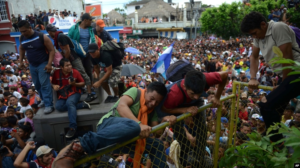 Thousands of Honduran migrants rush across the border toward Mexico, in Tecun Uman, Guatemala, Oct. 19, 2018.