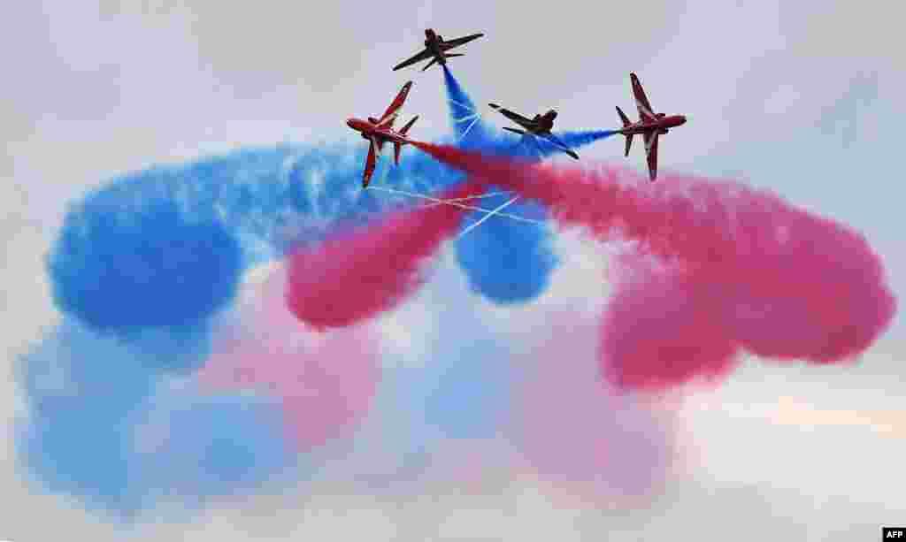 Tim Aerobatik Angkatan Udara Inggris, the Red Arrows, memamerkan kebolehan di udara sebelum acara balap mobil Grand Prix Formula Satu di sirkuit Silverstone, Inggris.