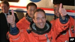 """Le commandant Jean-François Clervoy, de Toulouse, en France, lève ses deux pouces face aux photographes, pendant qu'il s'avance pour monter à bord de l'""""Astro-Van"""" avec ses collègues membres d'équipage avant le décollage de la navette spatiale Atlantis, 15 mars 1997"""