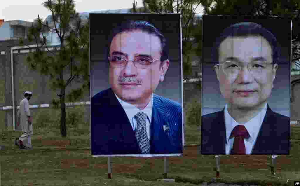 A man walks next to huge portraits of Chinese Premier Li Keqiang, right, and Pakistani President Asif Ali Zardari, left, displayed near the presidency in Islamabad, Pakistan.