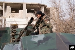 FILE - A Syrian army soldier stands on top of a vehicle carrying a gun in Salma, Syria.