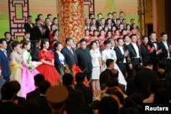 2018年6月19日,中国国家主席习近平和夫人彭丽媛,朝鲜领导人金正恩和夫人参加欢迎宴会,观赏文艺演出,和演员们合影。