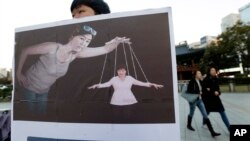 A South Korean college student holds a placard depicting South Korea's President Park Geun-hye, right bottom, as a marionette and Choi Soon-sil, who is at the center of a political scandal, as a puppeteer, in Seoul, South Korea, Nov. 3, 2016.