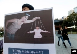 FILE - A South Korean college student holds a placard depicting South Korea's President Park Geun-hye, right bottom, as a marionette and Choi Soon-sil, who is at the center of a political scandal, as a puppeteer, in Seoul, South Korea, Nov. 3, 2016.