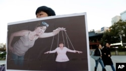 FILE - A South Korean college student holds a placard depicting South Korea's President Park Geun-hye, right bottom, as a marionette and Choi Soon-sil, who is at the center of a political scandal, as a puppeteer, in Seoul, South Korea.