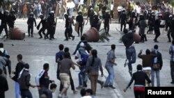 28일 이집트 카이로에서 무함마드 무르시 대통령의 새 헌법에 반대하는 시위대와 진압 경찰들.