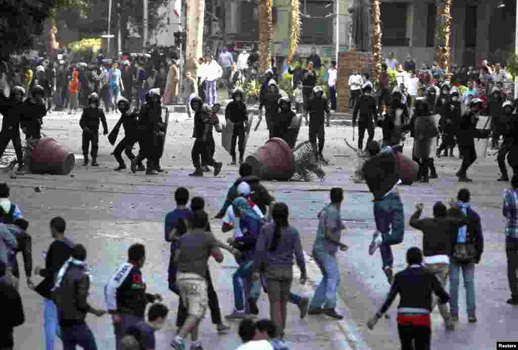 Riot police and protesters throw stones at one another during clashes near Tahrir Square, Cairo, Egypt, November 28, 2012.