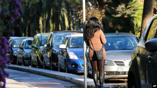 FILE - A prostitute waits for a client in a street of Nice southern France, Nov. 21, 2013. France's government is pushing one of Europe's toughest laws against prostitution and sex trafficking, and other countries are watching closely.