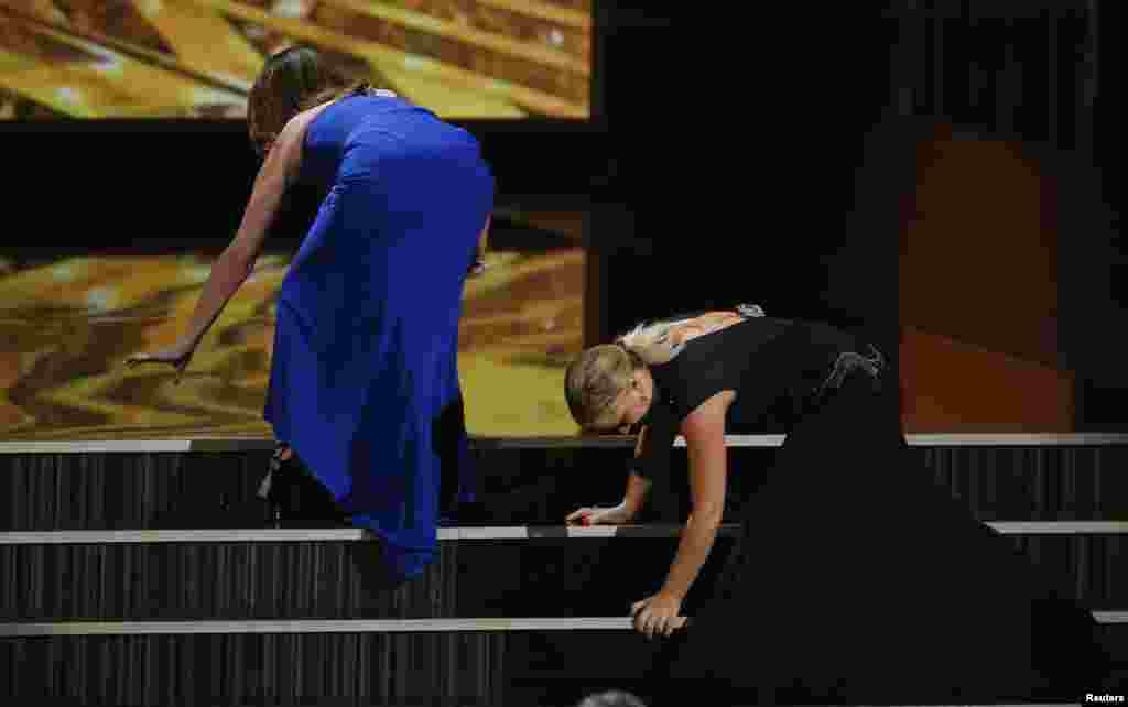 Actresses Tina Fey and Amy Poehler stumble as they take the stage to present the first award at the 65th Primetime Emmy Awards in Los Angeles, Sept 22, 2013.