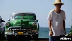 FILE - A man walks beside a U.S.-made car parked near the seaside on the outskirts of Havana.