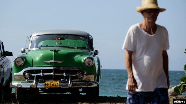 FILE - A man walks beside a U.S.-made car parked near the seaside on the outskirts of Havana.