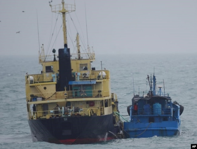 FILE - This photo released by Japan's Ministry of Defense shows what it says is the North Korean-flagged tanker Yu Jong 2, left, and the Min Ning De You 078 lying alongside in the East China Sea, Feb. 16, 2018.