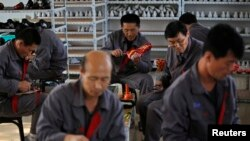 FILE - North Korean workers make soccer shoes inside a temporary factory at a rural village on the edge of Dandong October 24, 2012.