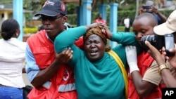 Le personnel Croix-Rouge kényane aide une femme en pleurs après qu'elle a vu le corps d'un parent tué dans l'attaque de jeudi dans une université, au Chiromo de maison funéraire, Nairobi, Kenya, jeudi 3 Avril 2015.