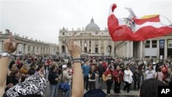 Pilgrims wave a Polish flag and sing as they gather in St. Peter's Square, at the Vatican, April 30, 2011, a day before late Pope John Paul II's beatification