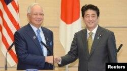 日本首相安倍晉三(右)在東盟高峰會上與與會的馬來西亞外長納吉(左)握手。