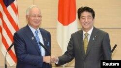 PM Jepang Shinzo Abe (kanan) berjabat tangan dengan PM Malaysia Najib Razak dalam rangkaian acara KTT Jepang-ASEAN di Tokyo 12/12/ 2013.
