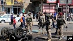 Warga sekitar dan pasukan keamanan memeriksa lokasi serangan bom mobil di Sadr City, Baghdad, 28 Agustus 2013.