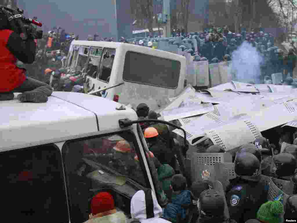 Pro-European integration protesters attack a police van during a rally near government administration buildings, Kyiv, Ukraine, Jan. 19, 2014.
