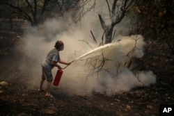 A woman uses a fire extinguisher to save a burning tree in Cokertme village, near Bodrum, Mugla, Turkey, Tuesday, Aug. 3, 2021. (AP Photo/Emre Tazegul)