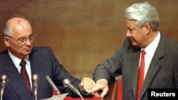 FILE - Boris Yeltsin and then Soviet President Mikhail Gorbachev touch hands during Gorbachev's address to the Extraordinary meeting of the Supreme Soviet of Russian Federation in Moscow, Aug. 23, 1991.