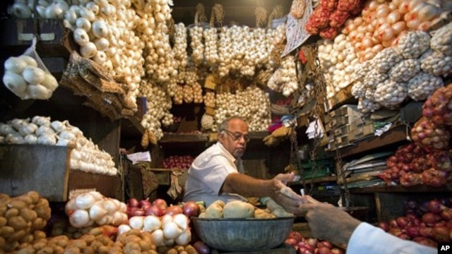 A vendor exchanges money with a customer at a shop selling garlic, onions and potatoes at a wholesale market in Mumbai (file photo)
