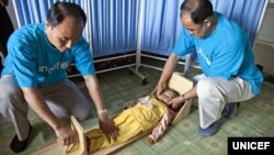 FILE - UNICEF staff measure a girl's height to see if she is stunted in a village health clinic of South Hamgyong province, North Korea.