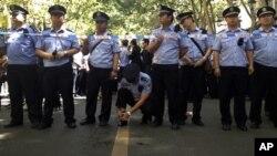 Cảnh sát Trung Quốc đứng gác trong khi dân chúng Côn Minh biểu tình vì lo ngại về vấn đề ô nhiễm