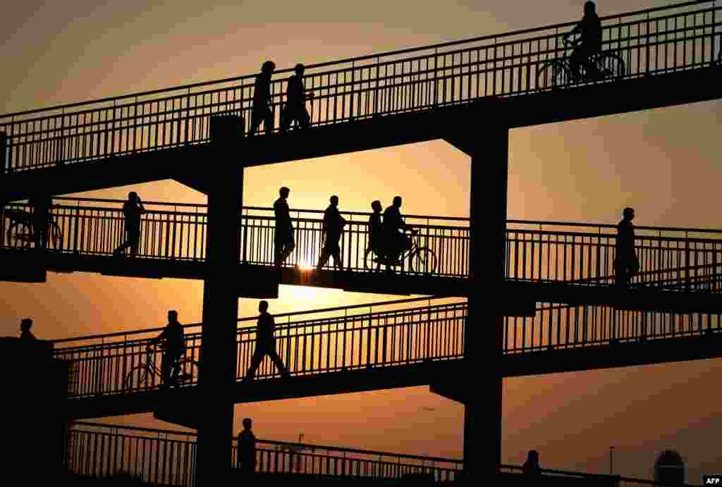 Laborers cross a pedestrian bridge in Dubai, United Arab Emirates.