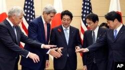 El primer ministro japonés, Shinzo Abe (centro) prepara juntar las manos con los secretarios Chuck Hagel y John Kerry, de EE.UU. y sus contrapartes, Fmio Kishida y Itsunori Onodera.