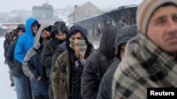 Migrants wait in line to receive plates of free food during a snowfall outside a derelict customs warehouse in Belgrade, Serbia, Jan. 18, 2017.