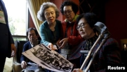 South Korean participants for a reunion check old pictures at a hotel used as a waiting place in Sokcho, South Korea, Oct. 19, 2015. The reunion of 90 South Koreans and 96 North Koreans, the 20th of its kind, will be held at a resort in the North.