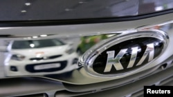 FILE - A Kia car is reflected at the showroom of the Avtomir company, a Kia cars dealership, in Moscow, Russia, March 11, 2016.