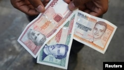 FILE - A man shows a new Cuban pesos outside a bank in Havana, Feb. 2, 2015.