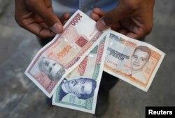 A man shows a new Cuban pesos outside a bank in Havana, Feb. 2, 2015.