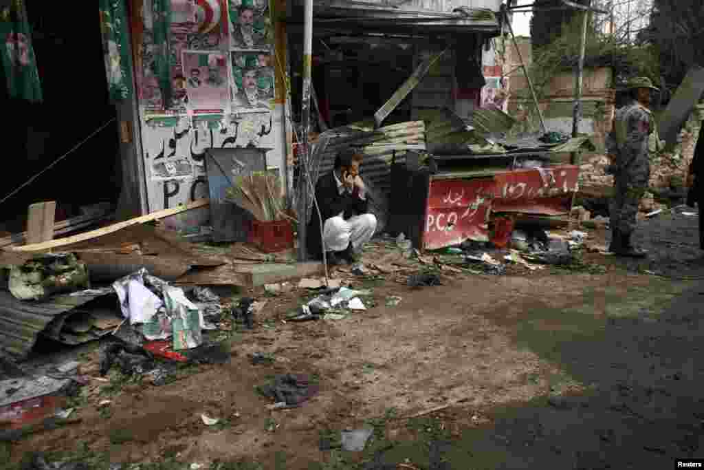 A shopkeeper sits outside his shop, after it was damaged by a bomb attack in Quetta, Pakistan, April 24, 2013.