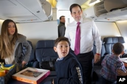 Republican presidential candidate, Sen. Marco Rubio, R-Fla. boards a plane with his family and staff to leave Manchester, N.H., Feb. 10, 2016, en route to South Carolina, after the New Hampshire primary. With him is daughter Amanda Rubio, 15, left, and s