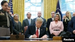 U.S. President Donald Trump signs the Trafficking Victims Protection Reauthorization Act in the Oval Office of the White House in Washington, Jan. 9, 2019.