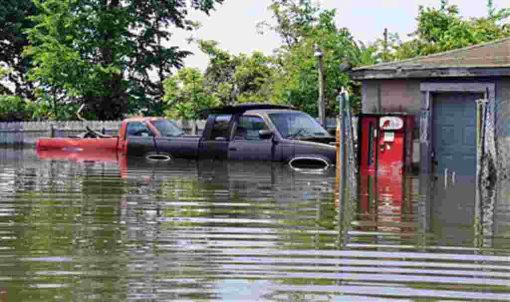 Dos camionetas se ven rodeadas de agua por la inundación del río Mississippi fuera de un garaje en Memphis, Tennessee, 8 de mayo de 2011.