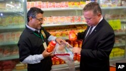 El ministro de Agricultura de Brasil, Blairo Maggi, acompañado por un agente de inspección sanitaria, recolecta productos de carne para pruebas, en un supermercado de Brasilia.