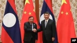 지난해 5월 중국을 방문한 분냥 보라칫 라오스 대통령(왼쪽)이 베이징 영빈관에서 시진핑 중국 국가주석과 만나 악수하고 있다.