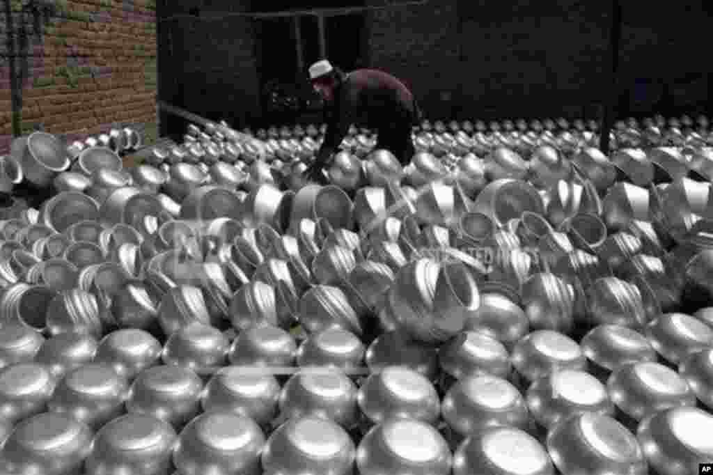 An Afghan laborer arranges pots at an aluminum factory, on Surkh Rod district of Jalalabad east of Kabul, Afghanistan.